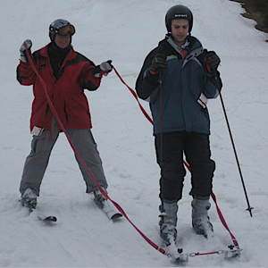 Visually impaired snow skier with guide and tethers.