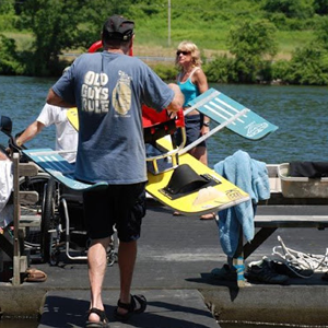 Volunteer carries sitski rig onto dock.